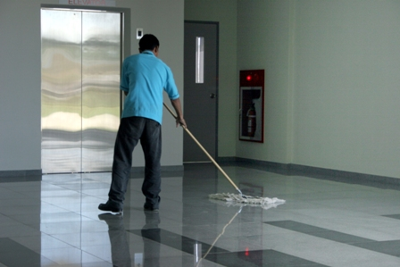 Man moping the tiled floor in a commercial building
